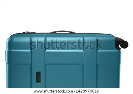 Fragment of turquoise plastic valise on wheels isolated on white background