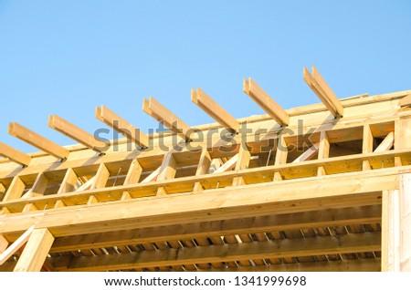 Fragment of wooden house framework on the sky background