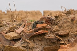 Fragments of ancient pottery in the ground. Artifacts. Finds of archaeologists. Fragments of old ceramic dishes. Remains of an ancient settlement in the steppe. History of the nomads. Archeology