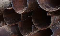 Fragments of old cast-iron water pipes. After many years of operation corroded metal pipe was destroyed. Rusty steel tube with holes of metallic corrosion.