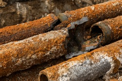 Fragments of old cast-iron water pipes. After many years of operation corroded metal pipe was destroyed. Rusty steel tube with holes of metallic corrosion. Rusty cast iron, metal