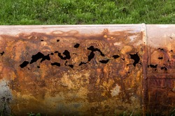 Fragments of old large water pipes. After many years of operation, corroded metal pipe destroyed. Rusty steel tube with holes metal corrosion. Selective focus.