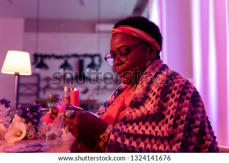 Fragrance. African american plump fortune-teller wearing golden watch looking pleased while holding a bag with fragrances #1324141676