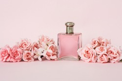 FRAGRANCE BOTTLE AND ELEGANT FLORAL ARRANGEMENT WITH PINK ROSES. ADVERTISING CONCEPT FOR WOMEN'S PERFUMES. PINK BACKGROUND.
