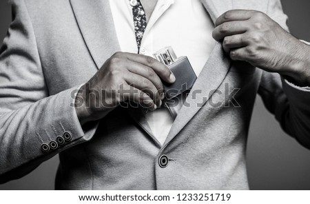 Fragrance smell. Men perfumes. Fashion cologne bottle. Man holding up bottle of perfume. Men perfume in the hand on suit background. Man in formal suit, bottle of perfume, closeup. Black and white.