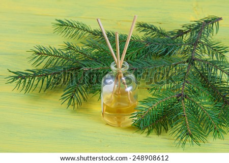 Fragrance sticks or bottle Scent diffuser with sprig fir on wooden background.