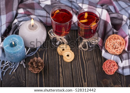Fragrant autumn and winter sangria with oranges, apples, cranberries and spices. Candle and glass of hot wine. Christmas evening.  #528312442
