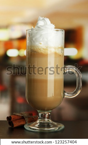 Fragrant coffee latte in glass cup with vanilla pods, on table in cafe