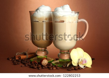 Fragrant coffee latte in glasses cups with spices, on brown background