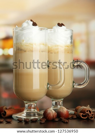 Fragrant coffee latte in glasses cups with spices, on table in cafe