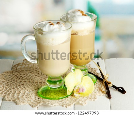 Fragrant coffee latte in glasses cups with spices, on wooden table