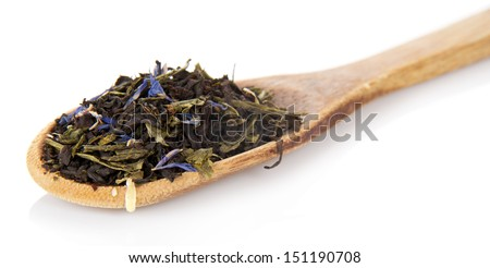 Fragrant dry tea leaves with cornflowers in the wooden spoon, isolated on white