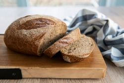 Fragrant homemade rye bread sliced on a wooden cutting board