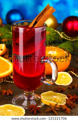Fragrant mulled wine in glass with spices and oranges around on wooden table on blue background