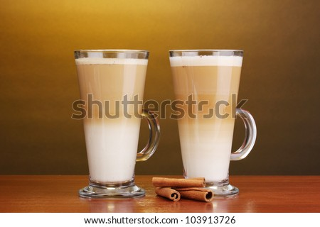 Fragrant ?offee latte in glass cups and cinnamon on wooden table on brown background