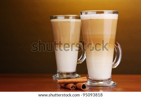 Fragrant ?offee latte in glass cups and cinnamon on wooden table on brown background #95093818