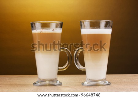 Fragrant ?offee latte in glass cups on wooden table on brown background
