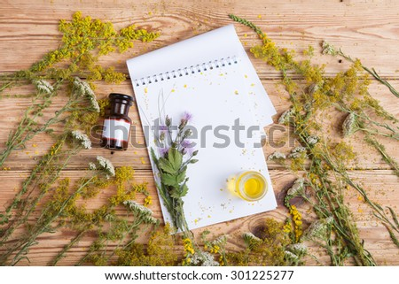 fragrant oil in the bottles, herbs and blank notepad