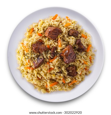 Fragrant pilaf with meat and vegetables top view on a plate. Isolated on white.