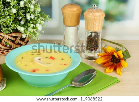 Fragrant soup in blue plate on table on window background close-up