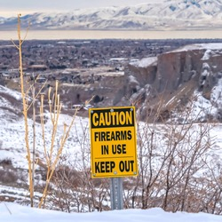 frame Caution Firearms In Use Keep Out sign on a mountain covered with snow in winter