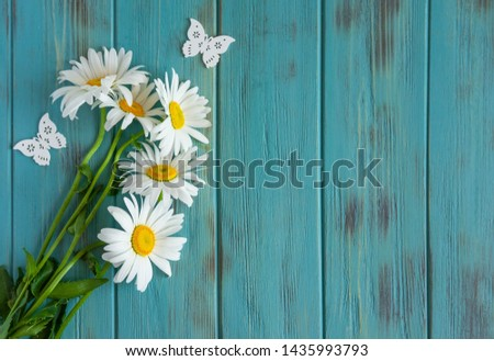 Frame for text with daisies. Daisies on a light wooden background. Design basis for greeting card. Floral banner, background. View from above