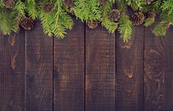 Frame from decorated Christmas tree on rustic wooden background with copy space for text. Happy New Year concept. Holiday background. Christmas mock-up or greeting card. Top view