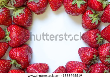 Frame from fresh strawberry with white copy space inside. Top view, Flat lay, Close-up. Place for custom text in middle. Raw fruits background. Delicious berries on white plate. Natural homegrown food