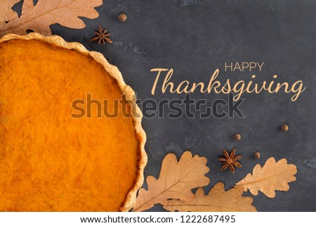 Frame from orange pumpkin pie, spices, autumn leaves on concrete dark gray background with text, toned. Happy Thanksgiving Day, culinary, recipe, menu concept. Top view, flat lay, copy space, mock up