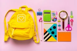Frame from school and office supplies Paper clips, scissors, pens, felt-tip pens, sharpener, calculator, stapler isolated on pink background Flat lay Top view Back to school, education concept Mock up