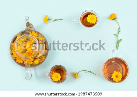 Frame made from cups of herbal tea, transparent teapot and calendula flowers on blue background. Calming drink concept. Copy space Top view Flat lay. Foto stock ©