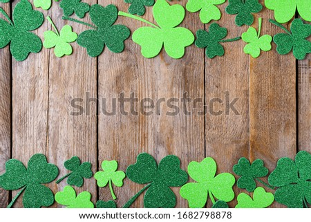Frame made of clover leaves on wooden table, flat lay with space for text. St. Patrick's Day celebration