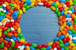 Frame made of colorful jelly beans on blue wooden background, flat lay. Space for text