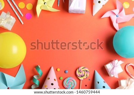 Frame made of different birthday party items on coral background, flat lay. Space for text