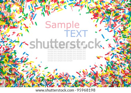 Frame made of little colorful sprinkles candy isolated on white background with sample text