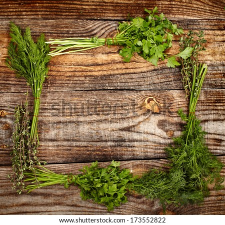 Frame made out of herbs on a wooden board with copyspace