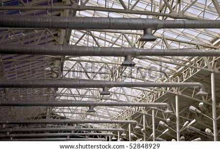 Frame of a metal truss. Roofs with top lighting. Part of the interior.
