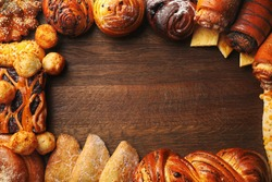 Frame of assorted fresh pastries on wooden background