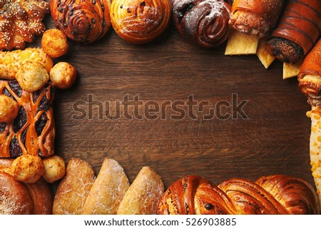 Frame of assorted fresh pastries on wooden background #526903885