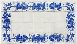 Frame of Azulejos (name of spanish tiles) with blue bunches of grapes