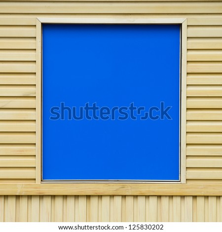Frame of blue boards against a backdrop of wooden wall.