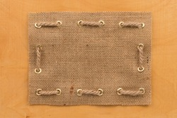 Frame of burlap, lying on  wooden, can be used as texture
