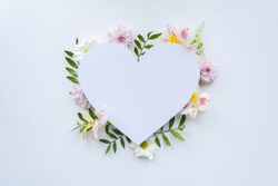 Frame of chamomiles, branches, leaves and lilac petals on white background. Flat lay, top view