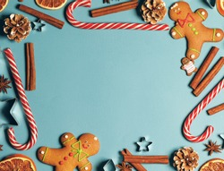 Frame of Christmas gingerbread cookies on blue background with copy space. Pattern of gingerbread men, candy canes, star mold, cinnamon, pine cone, orange. Top view, flat lay.