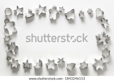 Frame of Christmas-themed cookie cutters on white. Holiday Xmas greeting card. Top view and flat lay. Photo stock ©