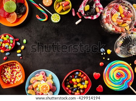 Frame of colorful bright assorted candy in bowls and jars, candy canes and rainbow colored spiral lollipops on black with scattered candy hearts and jellybeans around a central copy space on slate