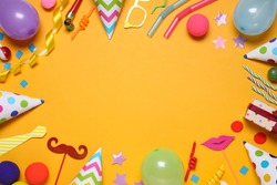 Frame of different party items and decorations with space for text on orange background, flat lay