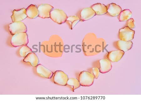 Frame of dried cream rose petals in heart shape with two pink paper hearts on pastel background. Love, romance or Valentine's day concept, mock up. Flat lay, copy space, top view #1076289770