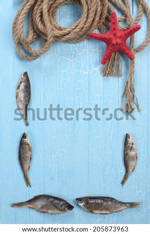 frame of dried fish, starfish and twisted rope on the background of painted wooden tablets