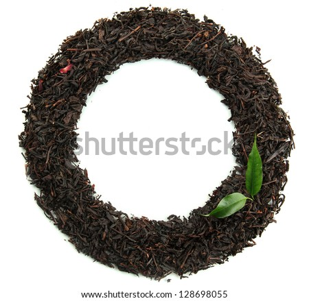 Frame of dry black tea with green leaves, isolated on white